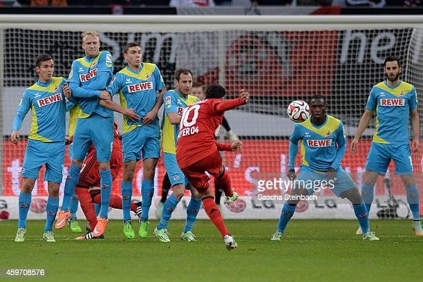 Hakan Calhanoglu of Leverkusen fires in a free kick towards the Koeln wall prior Karim Bellarabi scores his team's first goal during the Bundesliga...