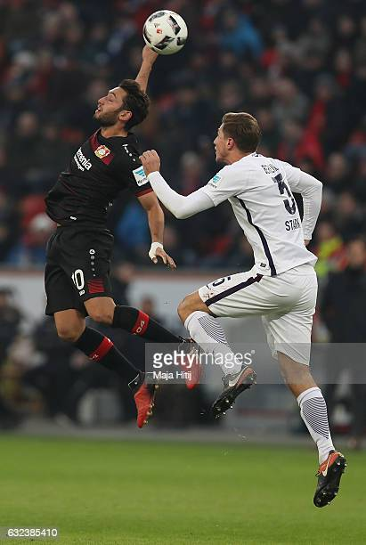 Hakan Calhanoglu of Leverkusen is challenged by Niklas Stark of Berlin during the Bundesliga match between Bayer 04 Leverkusen and Hertha BSC at...