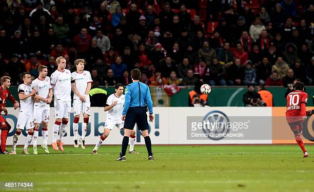 Hakan Calhanoglu of Leverkusen scores his team's opening goal during extra time during the round of 16 DFB Cup match between Bayer 04 Leverkusen and...