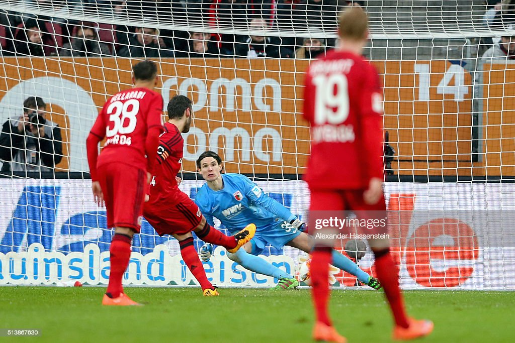 Hakan Calhanoglu of Leverkusen scores the 3rd team goal with a penalty against Marwin Hitz, keeper of Ausgburg during the Bundesliga match between FC Augsburg and Bayer Leverkusen at WWK Arena on March 5, 2016 in Augsburg, Germany.