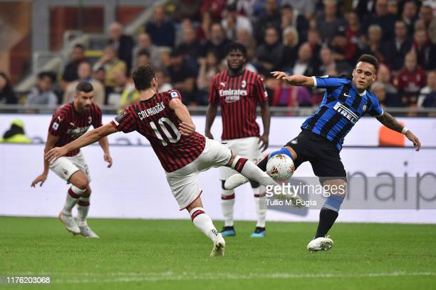 Hakan Calhanoglu of Milan and Lautaro Martinez of Internazionale compete for the ball during the Serie A match between AC Milan and FC Internazionale...
