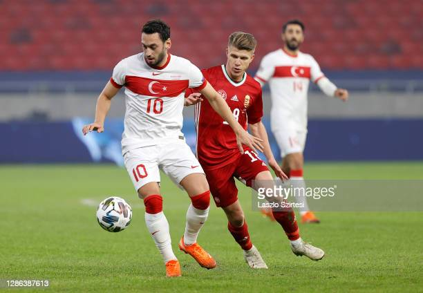Hakan Calhanoglu of Turkey is challenged by David Siger of Hungary during the UEFA Nations League group stage match between Hungary and Turkey at...