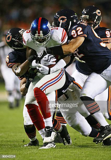 Hakeem Nicks of the New York Giants is tackled by Josh Bullocks and Hunter Hillenmeyer of the Chicago Bears during a preseason game on August 22 2009...
