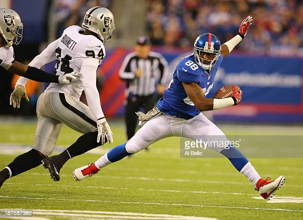 Hakeem Nicks of the New York Giants runs after a catch against Kevin Burnett of the Oakland Raiders during their game at MetLife Stadium on November...