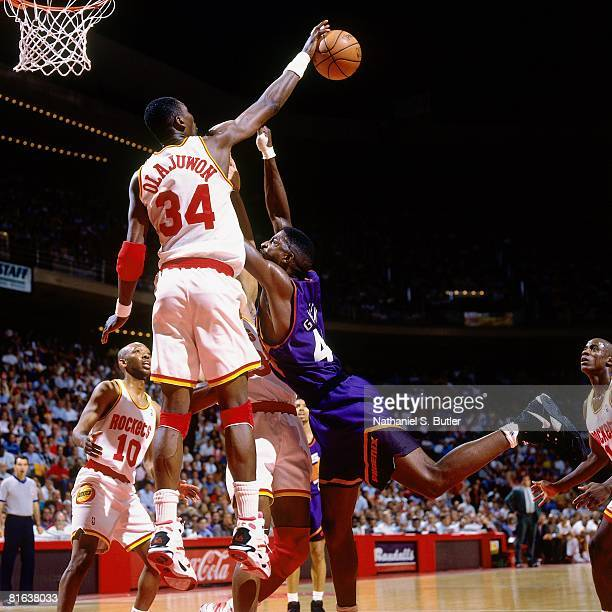 Hakeem Olajuwon of the Houston Rockets blocks a shot attempt by AC Green of the Phoenix Suns in Game Five of the Western Conference Semifinals during...