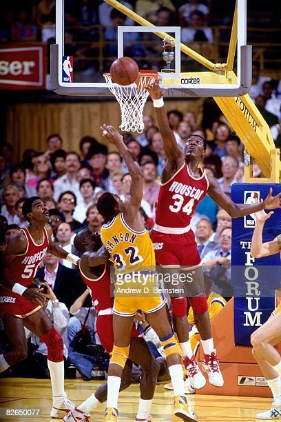 Hakeem Olajuwon of the Houston Rockets blocks a shot attempt by Magic Johnson of the Los Angeles Lakers during the 1986 season at the Great Western...