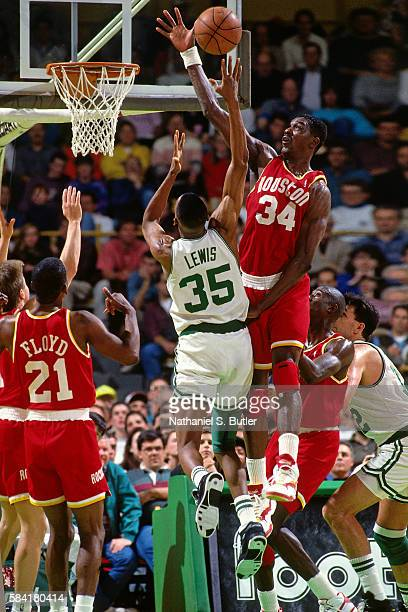 Hakeem Olajuwon of the Houston Rockets blocks a shot attempt by Reggie Lewis of the Boston Celtics during a game played circa 1993 at the Boston...