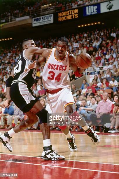 Hakeem Olajuwon of the Houston Rockets drives to the basket against the San Antonio Spurs during an NBA game at the Compaq Center circa 1995 in...