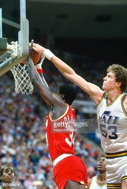 Hakeem Olajuwon of the Houston Rockets has his shot blocked by Mark Eaton of the Utah Jazz during an NBA basketball game circa 1990 at the Salt...