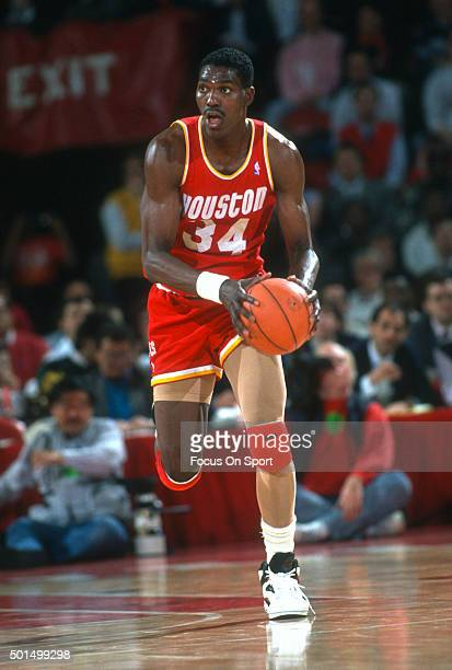 Hakeem Olajuwon of the Houston Rockets looks to pass the ball against the Washington Bullets during an NBA basketball game circa 1987 at the Capital...