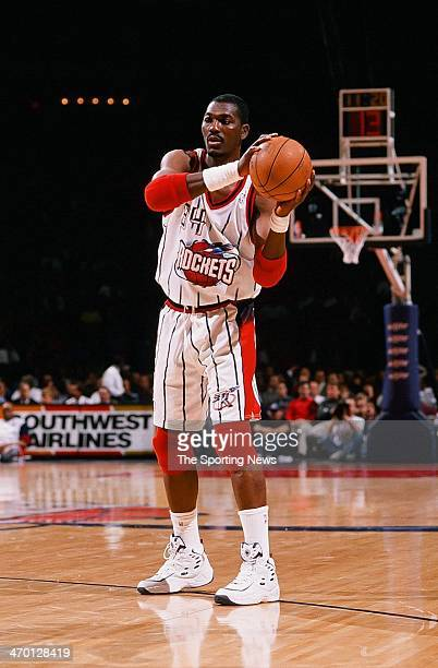Hakeem Olajuwon of the Houston Rockets moves the ball during the game against the New Jersey Nets on March 12 1998 at Compaq Center in Houston Texas