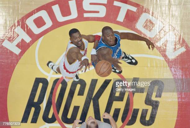 Hakeem Olajuwon of the Houston Rockets of the Western Conference contests the ball at the tip off against Shaquille O'Neal of the Orlando Magic of...
