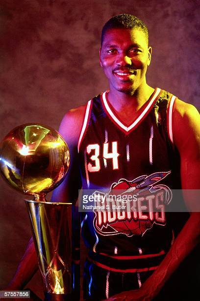 Hakeem Olajuwon of the Houston Rockets poses for a portrait displaying the teams new uniforms and the Larry O'Brien trophy prior to the start of the...