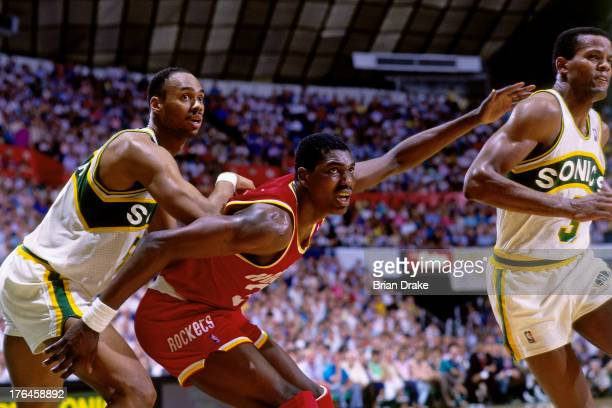 Hakeem Olajuwon of the Houston Rockets posts up against Alton Lister of the Seattle SuperSonics during a game played in 1987 at the Seattle Coliseum...