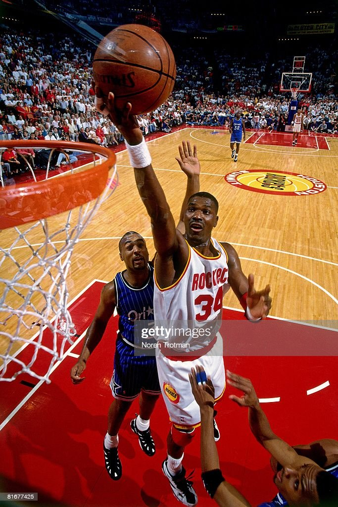 Hakeem Olajuwon #34 of the Houston Rockets shoots a layup against the Orlando Magic defense in Game Four of the 1995 NBA Finals at the Summitt on June 14, 1995 in Houston, Texas. The Rockets won 113-101.