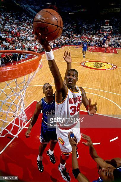Hakeem Olajuwon of the Houston Rockets shoots a layup against the Orlando Magic defense in Game Four of the 1995 NBA Finals at the Summitt on June 14...
