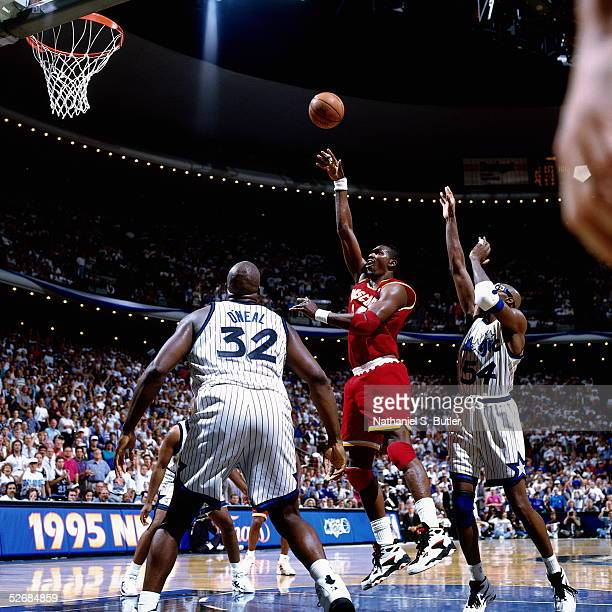 Hakeem Olajuwon of the Houston Rockets shoots a one handed jump shot in the lane against Shaquille O'Neal of the Orlando Magic during Game 1 of...