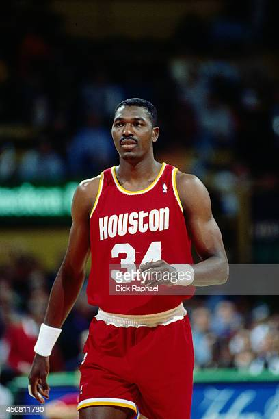 Hakeem Olajuwon of the Houston Rockets stands on the court during a game against the Boston Celtics circa 1995 at the Boston Garden in Boston...
