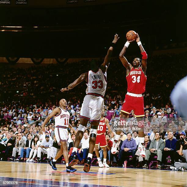 Hakeem Olajuwon of the Houston Rockets takes a jumpshot over Patrick Ewing of the New York Knicks during an NBA game at Madison Square Garden circa...