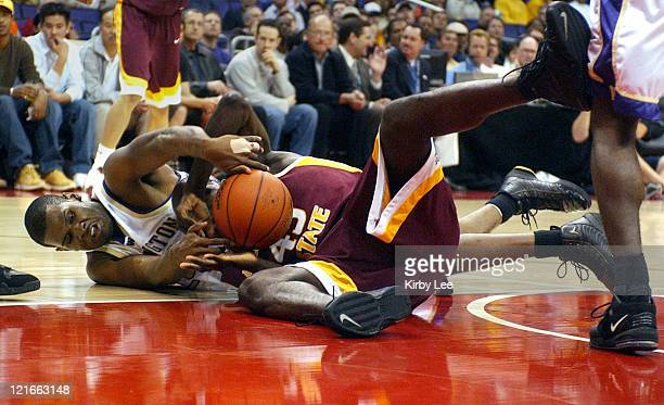 Hakeem Rollins of Washington and Serge Angounou of Arizona State battle for loose ball during firstround game in the Pacific Life Pac10 men's...