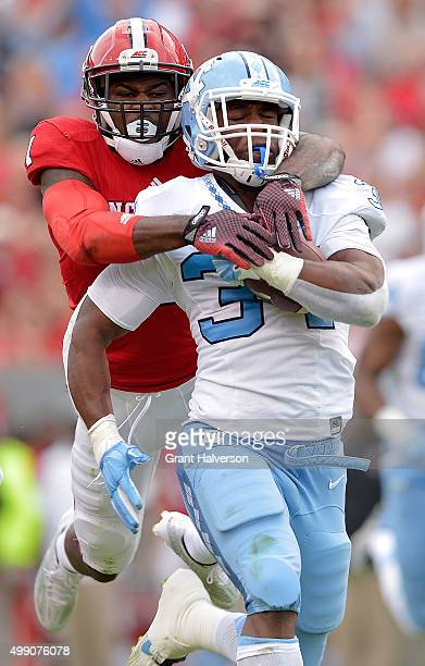 Hakim Jones of the North Carolina State Wolfpack tackles Elijah Hood of the North Carolina Tar Heels during their game at CarterFinley Stadium on...