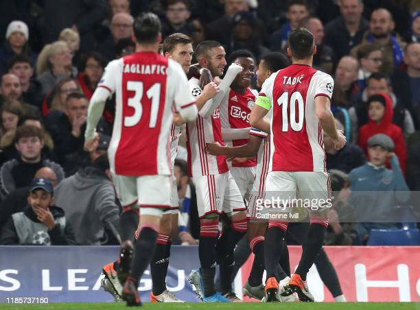 Hakim Ziyech of AFC Ajax celebrates with teammates after his freekick results in their third goal after Kepa Arrizabalaga of Chelsea scores an own...