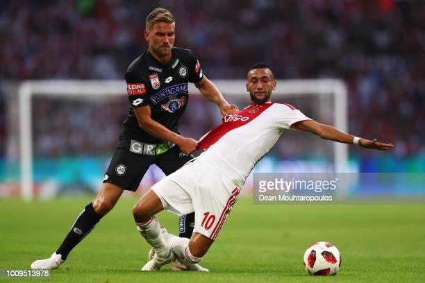 Hakim Ziyech of Ajax and Peter Zulj of SK Sturm Graz battle for possession during the first leg UEFA Champions League Qualifier match between Ajax...