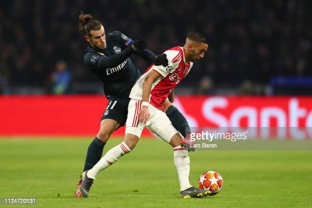 Hakim Ziyech of Ajax is challenged by Gareth Bale of Real Madrid during the UEFA Champions League Round of 16 First Leg match between Ajax and Real...