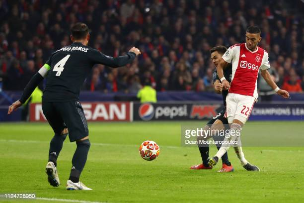 Hakim Ziyech of Ajax scores his team's first goal as Sergio Ramos of Real Madrid attempts to block during the UEFA Champions League Round of 16 First...