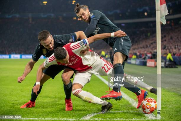 Hakim Ziyech of Ajax tackled by Gareth Bale and Dani Carvajal of Real during the UEFA Champions League Round of 16 match between Ajax Amsterdam and...