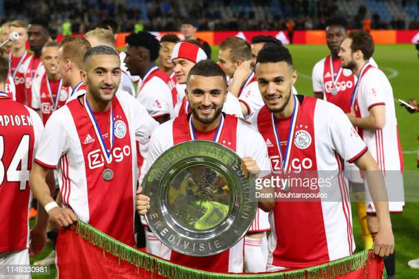 Hakim Ziyech of Ajax Zakaria Labyad of Ajax and Noussair Mazraoui of Ajax celebrate with the trophy after winning the Eredivisie following the...