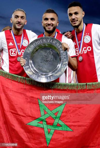 Hakim Ziyech of Ajax Zakaria Labyad of Ajax Noussair Mazraoui of Ajax celebrates the championship with the Eredivisie Trophy during the Dutch...