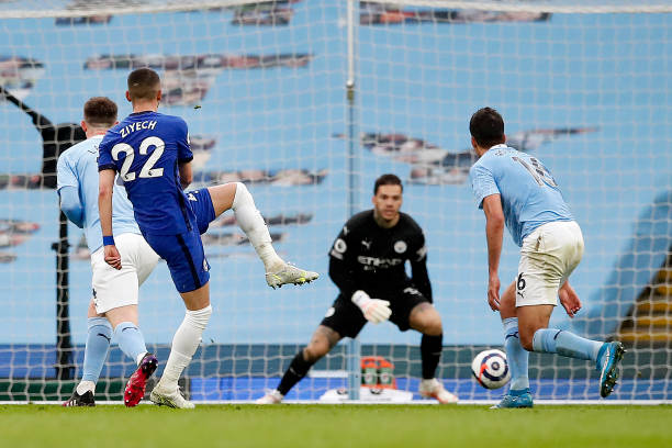 Hakim Ziyech of Chelsea scores their side's first goal past Ederson of Manchester City during the Premier League match between Manchester City and...