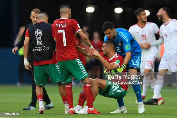 Hakim Ziyech of Morocco and Morocco goalkeeper Munir help dejected teammate Aziz Bouhaddouz of Morocco to his feet at the end of the 2018 FIFA World...
