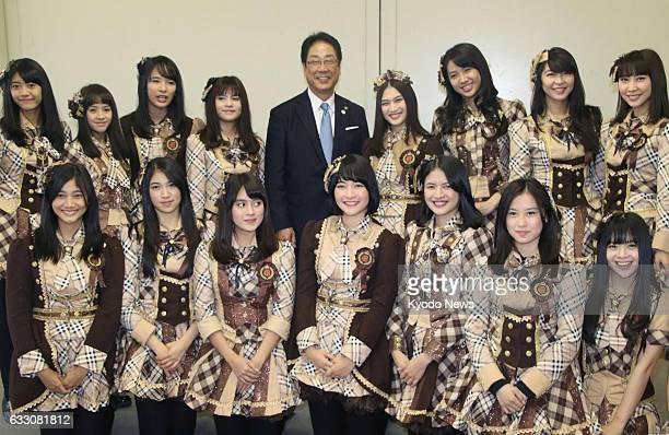 Hakodate Mayor Toshiki Kudo poses for photos with members of Jakartabased allgirl pop group JKT48 a sister unit of Japan's AKB48 at the Hakodate...
