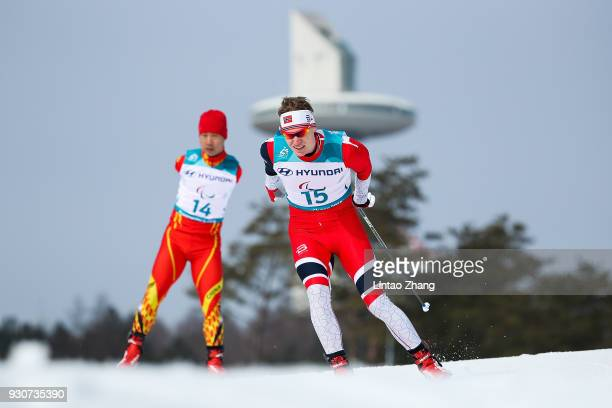Hakon Olsrud of Norway and Du Haitao of China competes in the Men's Cross Country 20km Free Standing event at Alpensia Biathlon Centre during day...