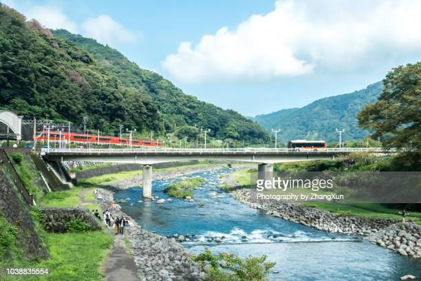 hakone skyline with mountain, river, clear sky and red train, travel bus in kanagawa-ken, japan at day time. - 郊外の風景 ストックフォトと画像