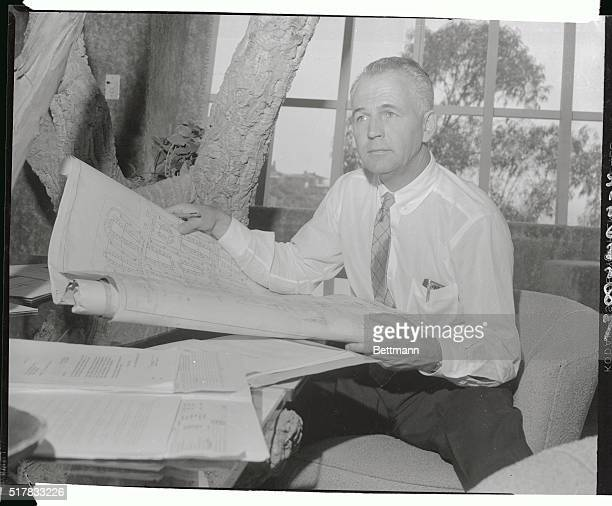 Hal B Hayes designer and builder of unusual dwellings looks over plans of American's first atom bombproof city which he has been commissioned to...