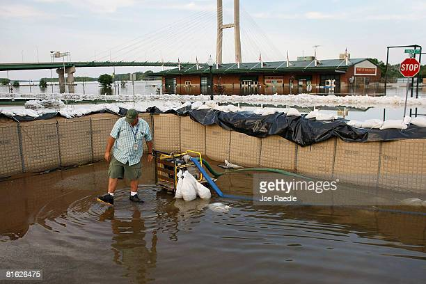 Hal Geren steps back from a sump pump after starting it up to move water that is flowing from the Mississippi River under a makeshift wall June 18...