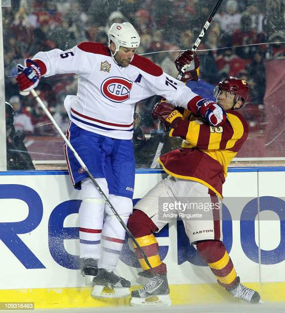 Hal Gill of the Montreal Canadiens hits Jarome Iginla of the Calgary Flames during the 2011 NHL Heritage Classic Game at McMahon Stadium on February...