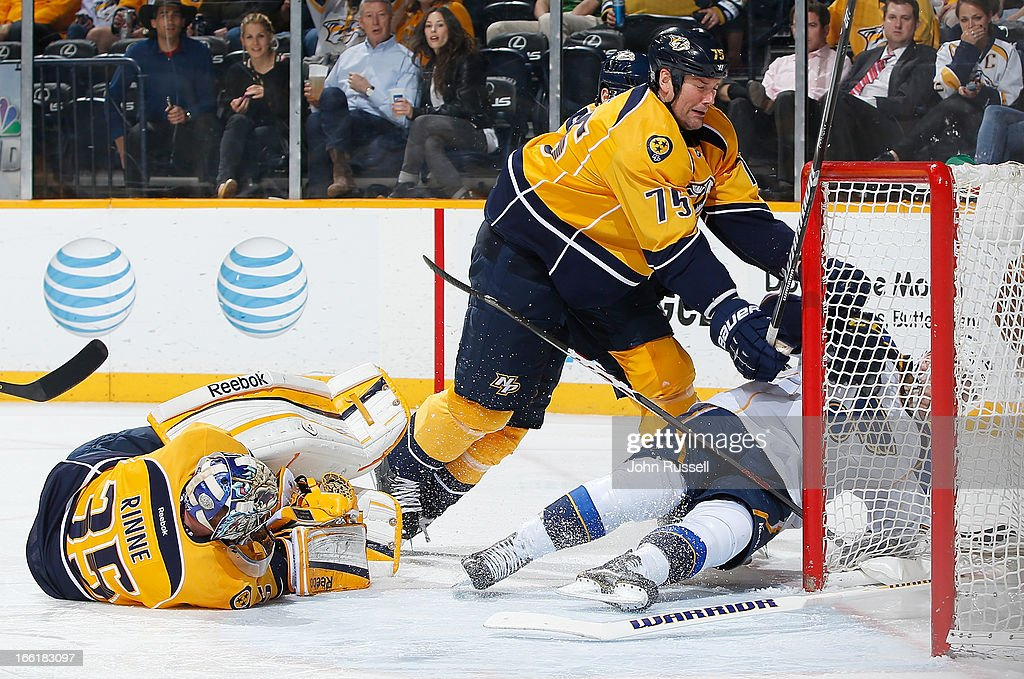 Hal Gill #75 of the Nashville Predators takes down Adam Cracknell #79 of the St. Louis Blues as goalie Pekka Rinne #35 covers the puck during an NHL game at the Bridgestone Arena on April 9, 2013 in Nashville, Tennessee.