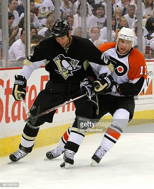 Hal Gill of the Pittsburgh Penguins battles for the puck with Jeff Carter of the Philadelphia Flyers during Game Five of the Eastern Conference...