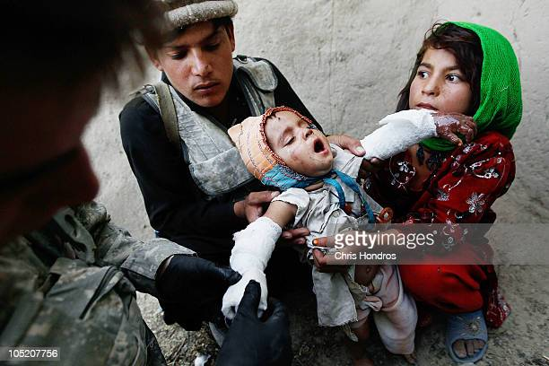 Halawasha an Afghan Pashtun girl and an Afghan National Police member holds her badly burned young sister Shokria while a medic in the US Army's...