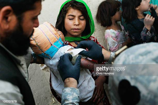 Halawasha an Afghan Pashtun girl holds her badly burned young sister Shokria as soldiers in the US Army's 101st Airborne Division begin to examine...