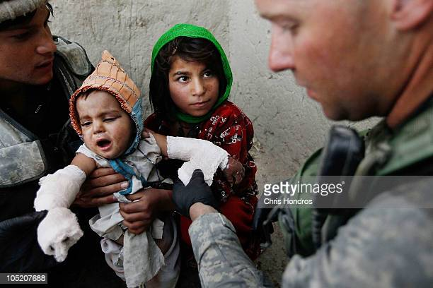 Halawasha an Afghan Pashtun girl holds her badly burned young sister Shokria while Sgt Scott MacKinnon of Wayland New York in the US Army's 101st...