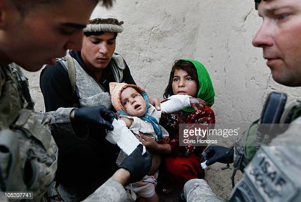 Halawasha an Afghan Pashtun girl holds her badly burned young sister Shokria while medics Pfc Benjamin Fisher of Zanesville Ohio and Sgt Scott...