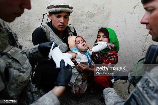 Halawasha an Afghan Pashtun girl holds her badly burned young sister Shokria while medic Pfc Benjamin Fisher of Zanesville Ohio and Sgt Scott...