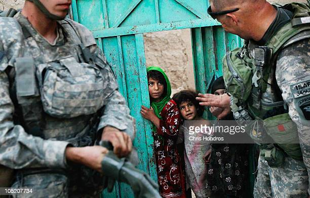 Halawasha an Afghan Pashtun girl watches as medic Pfc Benjamin Fisher of Zanesville Ohio and Sgt Scott MacKinnon of Wayland New York in the US Army's...