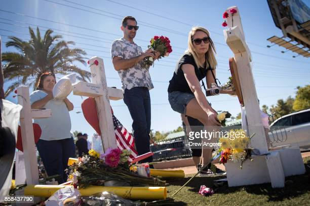 Halee Harczynski leaves a rose at each of the 58 white crosses for the victims of Sunday night's mass shooting at a makeshift memorial on the south...