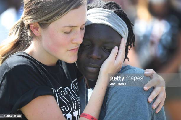 Haley Avery hugs her cousin Selah Moore as they pray together during a Juneteenth event Organized by the One Race Movement at Centennial Olympic Park...